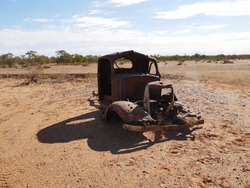 An old abandoned rusted out shell of an old ute truck slowly rotting and rusting on the red dirt of the desert with a line of green trees along a dried up river bed and blue sky on Central Australia