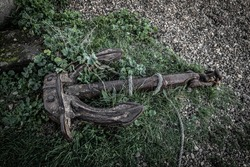 An old abandoned rusty anchor lying in grass