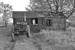 An old abandoned tractor and shed in black and white. A rural scene.