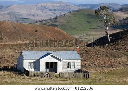 An old abandoned weatherboard farm house  in an Australian rural landscape