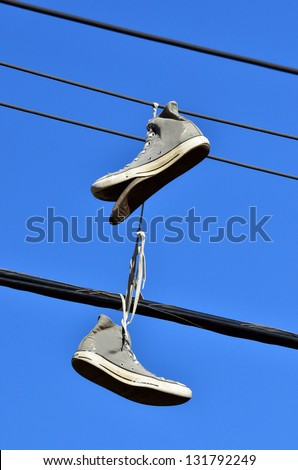 An old all star shoes hanged on electric line. Concept photo of youth, teenage, vandalism ,rebellion,  footwear,  and shoe tossing