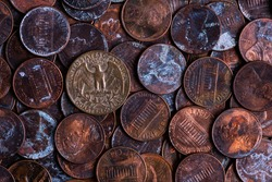 An old 25 American cent coin depicting an eagle on a pile of rusty 1 cent coins