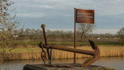 An old anchor along the river Linge. The iron flag tells us the story of the luxury steamboat Leerdam that sank on the North Sea in 1886.
