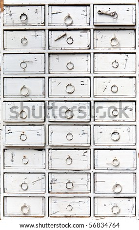 an old, ancient wooden chest of drawers, painted white - stock photo