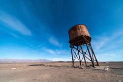 An old and abandoned railway track and station with it water tank to fill the trains during their travel around the Atacama Desert for transporting niter or saltpeter coming from the mining industry