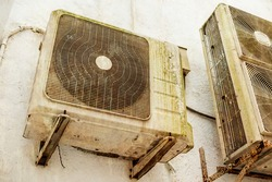 An old and aging Split type air conditioner condenser mounted on the exterior wall. Grimy and covered in slight moss and rust. Rusting brackets.