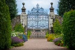 An old and elegant wrought iron gate stands at the end of an entranceway lined with hedges, trees and flowers