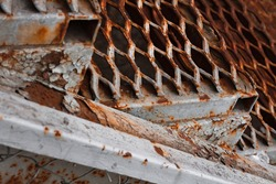 An old and rusted fire escape made of metal with a textured weathered surface, close-up. An iron staircase with a mesh painted surface, all covered with rust spots and streaks, with peeled paint