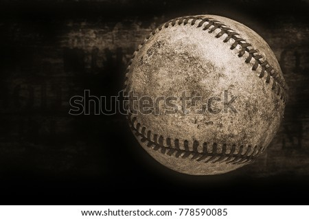 an old and used vintage baseball on a wooden background