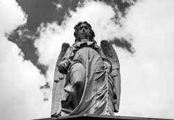 An old angel sculpture looking down in low angle shooting in top of mausoleum cemetery. Blue and cloudy sky at background. Black and White photography