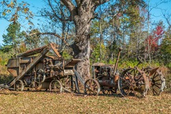 An old antique harvester and tractor no longer in use rusty and weathered abandoned in a farm field next to a large old tree on a bright sunny day in autumn