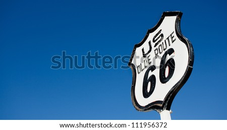 An old, antique, nostalgic route 66 sign in front of blue sky