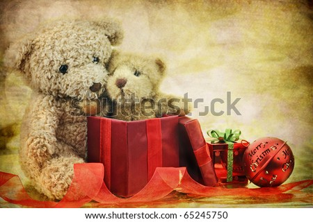 An old antique teddy bear hugs his Christmas gift, a new little teddy bear friend, while surrounded by ornaments and ribbons . Copy space available.