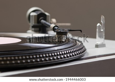 An old antique turntable with melodies - gramophone. Vintage record player spins. Stock photo ©