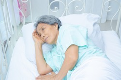 An old Asian woman wearing a green shirt Sleeping on the bed in the room. Elderly people are not comfortable. Women have white hair on their heads.