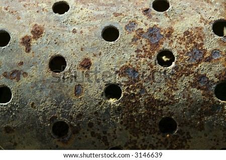 An old badly rusted and corroded perforated steel cylinder