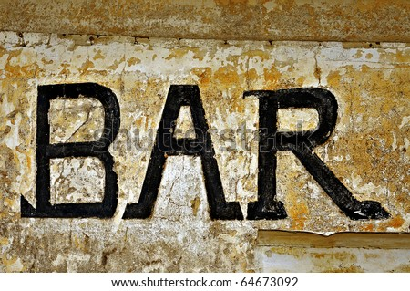 an old bar sign over a dirty wall - stock photo