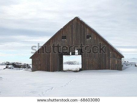 An old barn weathers in the cold winter.