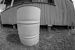An old barrel in front of a corrugated iron building, circular with fisheye lens