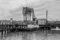 An old bascule railroad bridge (also referred to as a drawbridge or a lifting bridge) on a gray day with a counterweight. To provide clearance for boat traffic. In black and white.