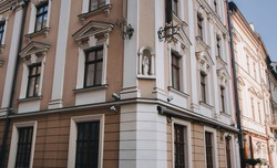 An old beautiful building with windows and decorative fittings and a sculpture of the Virgin Mary and Child in a niche. Lviv, Ukraine.