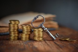 An old beautiful old key, a stack of gold coins, an old book. Business start-up, investment, treasure hunting, or the concept of the key to success.