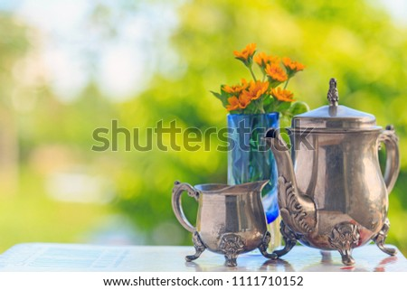 An old beautiful teapot and teacup and yellow flowers in a blue glass pot on a white book with nature background. #1111710152