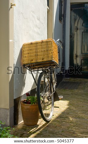 An old bike with a basket on the handle bar leaning against a plastered wall