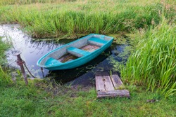 An old blue boat is tied with a rusty chain to a metal pole. The boat is standing in a small grassy pond. There are remains of a wooden bridge.