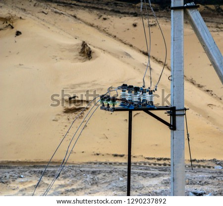 An old blue rusty transformer supplies electricity through the traverse, wires and electric supports in a sand quarry. #1290237892
