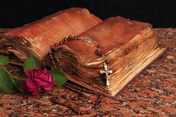 An old book, a crucifix and a dried rose on a granite table.