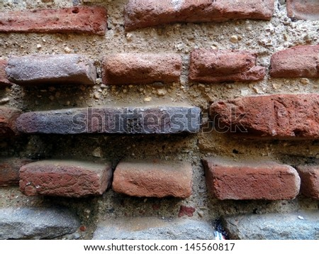An old brick wall totes its age by means of protruding bricks.