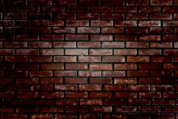 An old brick wall with deep vignetting in dark colors. Background brick dark vocus light in the middle of the frame