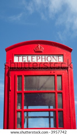 An old British red telephone box and a blue sky.