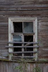 An old broken boarded up window in a wooden house in Russia. The window of a non-residential abandoned house.