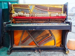 An old broken piano is on the street. Front view