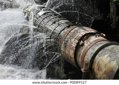 An old broken pipe that leaks water in all directions.