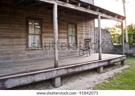 An old broken stone wall stands outside a wooden home from the early 1900's in historic area of estero florida. There is an old wooden rocking chair on porch. Koreshan state Park.