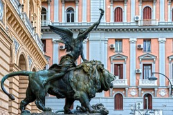 An old, bronze statue of a winged goddess sitting on a lion in the center of Naples, Italy.