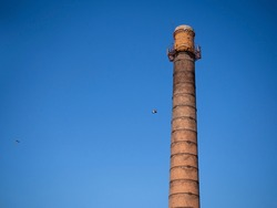 An old brown brick chimney a huge chimney from which pigeons fly against the blue sky