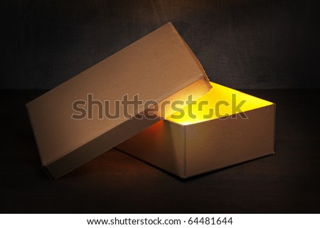 An Old brown cardboard box with glowing contents.