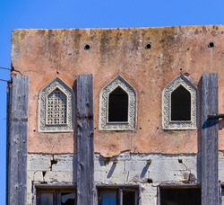 An old building with arabic shaped windows in disrepair.