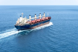 An old bulk carrier or bulker sails in the sea to trade around the world