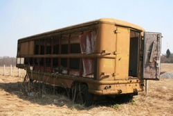 an old burnt out bus stands in a field
