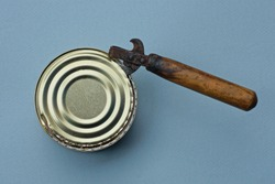 an old can opener with a brown wooden handle opens a yellow aluminum lid on a tin can on a gray table