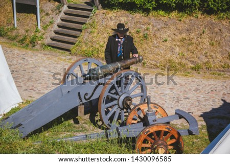 An old cannon that shoots cores. Antique weapons. Artillery guns. An old man in a hat. #1430096585