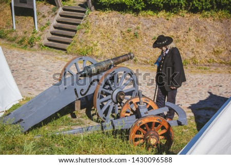 An old cannon that shoots cores. Antique weapons. Artillery guns. An old man in a hat. #1430096588