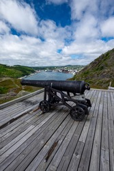 An old canon used to protect St. John's Harbour sits upon a hill looking out over the water. The sky is blue and the sun can be seen setting over the City. Oil supply boats are moored in the harbour.