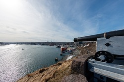 An old canon used to protect St. John's Harbour sits upon a hill looking out over the water. The sky is blue and the sun can be seen setting over the City. Oil supply boats are moored in the harbor.