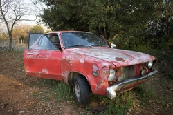 An old car with faded red colour and open doors. At a vehicle graveyard.